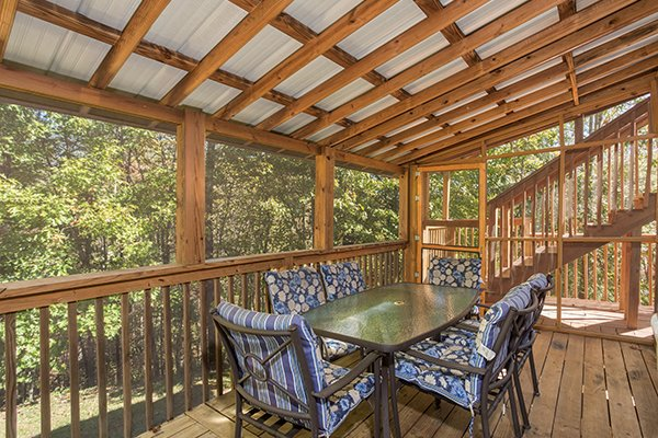 Outdoor dining space for six on the screened deck at Living on Love, a 2 bedroom cabin rental located in Pigeon Forge
