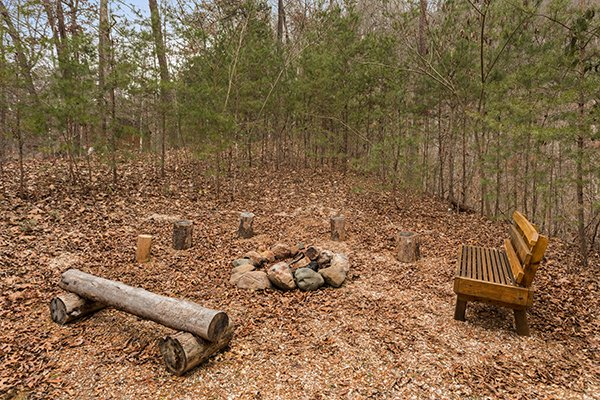 Fire pit with bench and log seating at Rising Wolf Lodge, a 3 bedroom cabin rental located in Pigeon Forge