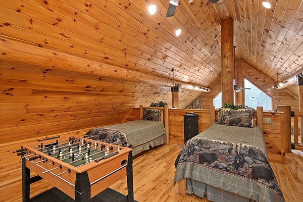 Foosball table and beds in the loft space at Rising Wolf Lodge, a 3 bedroom cabin rental located in Pigeon Forge