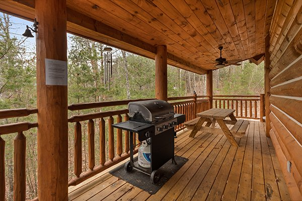 Covered deck with propane grill and picnic table at Rising Wolf Lodge, a 3 bedroom cabin rental located in Pigeon Forge