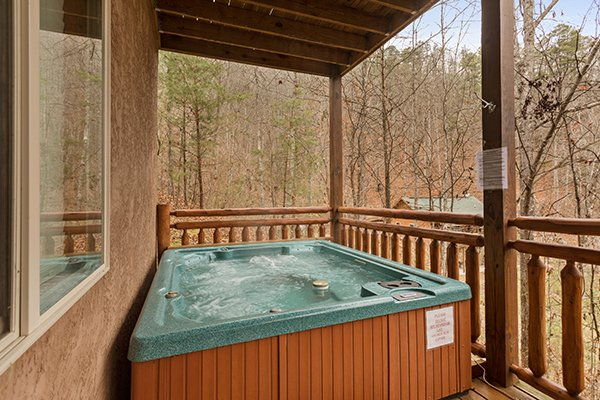 Hot tub on a covered deck at Rising Wolf Lodge, a 3 bedroom cabin rental located in Pigeon Forge