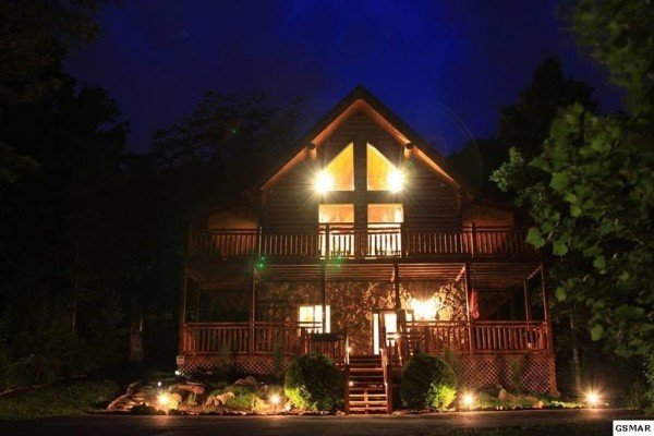 Rising Wolf Lodge, a 3 bedroom cabin rental located in Pigeon Forge, lit at night