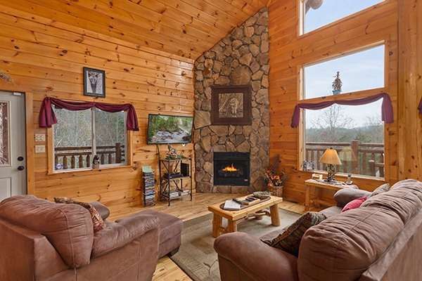 Living room with stone fireplace and TV at Rising Wolf Lodge, a 3 bedroom cabin rental located in Pigeon Forge