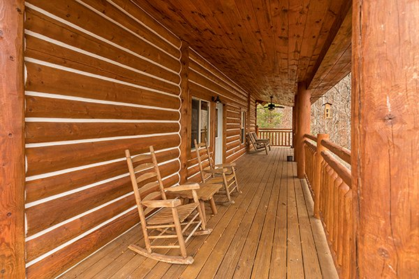 Rocking chairs on a covered deck at Rising Wolf Lodge, a 3 bedroom cabin rental located in Pigeon Forge