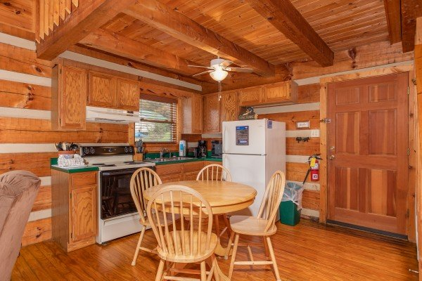 Dining table with space for four and kitchen with white appliances at Fishin' & Wishin', a 1-bedroom cabin rental located in Sevierville