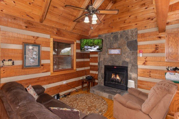 Fireplace and television in the living room at Fishin' & Wishin', a 1-bedroom cabin rental located in Sevierville