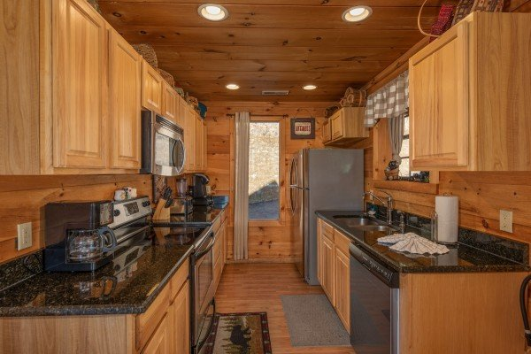 Galley kitchen with stainless appliances at A Perfect Getaway, a 3 bedroom cabin rental located in Pigeon Forge
