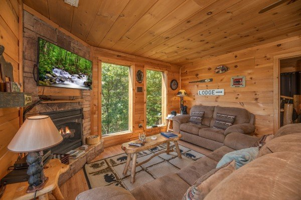 Living room with fireplace, TV, sofa, and loveseat at A Perfect Getaway, a 3 bedroom cabin rental located in Pigeon Forge