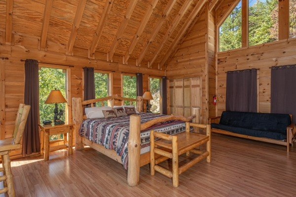 Loft bedroom with a king log bed, two night stands, lamps, a futon, and bench at A Perfect Getaway, a 3 bedroom cabin rental located in Pigeon Forge