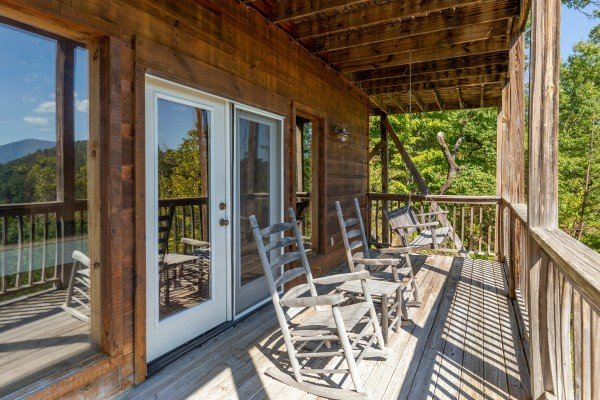 Lower deck with rocking chairs & a swing at A Perfect Getaway, a 3 bedroom cabin rental located in Pigeon Forge