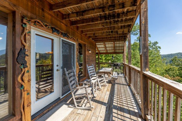 Rocking chairs on a covered deck at A Perfect Getaway, a 3 bedroom cabin rental located in Pigeon Forge