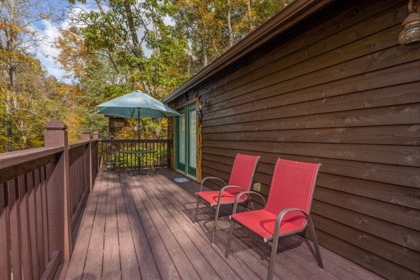 Dining table with umbrella and two chairs on a deck at Hidden Pines, a 2-bedroom cabin rental located in Pigeon Forge