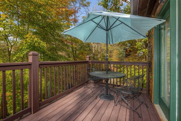 Dining table for 2 with umbrella at Hidden Pines, a 2-bedroom cabin rental located in Pigeon Forge