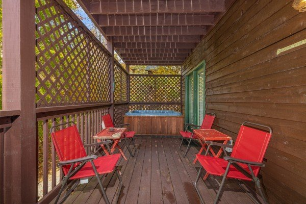 Chairs and hot tub on a deck at Hidden Pines, a 2-bedroom cabin rental located in Pigeon Forge