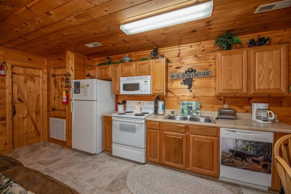 Kitchen with white appliances at Hidden Pines, a 2-bedroom cabin rental located in Pigeon Forge