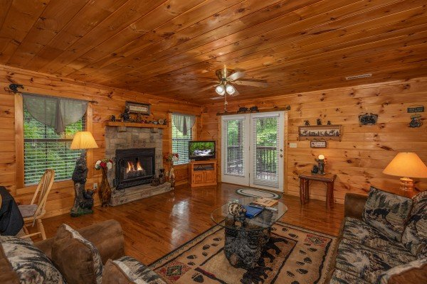 Living room with fireplace, TV, and deck access at Hidden Pines, a 2-bedroom cabin rental located in Pigeon Forge