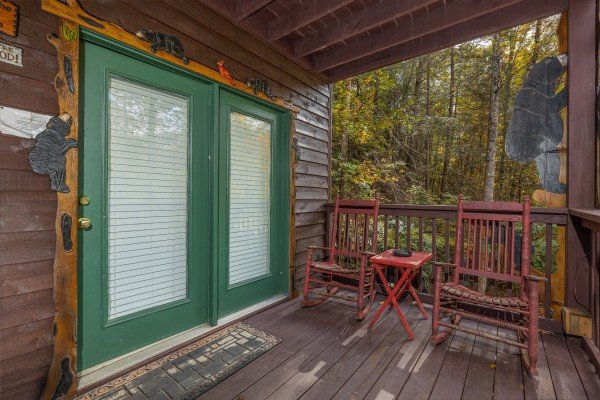 Lower deck with two rocking chairs at Hidden Pines, a 2-bedroom cabin rental located in Pigeon Forge