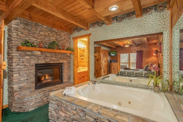 Fireplace and jacuzzi in the bedroom at Sweet Mountain Escape, a 2 bedroom cabin rental located in Pigeon Forge