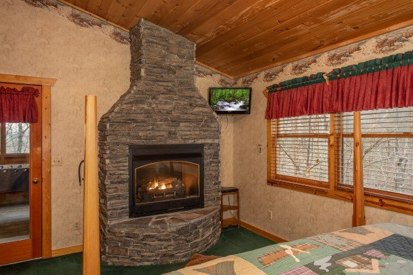 Fireplace and TV in the upper bedroom at Sweet Mountain Escape, a 2 bedroom cabin rental located in Pigeon Forge