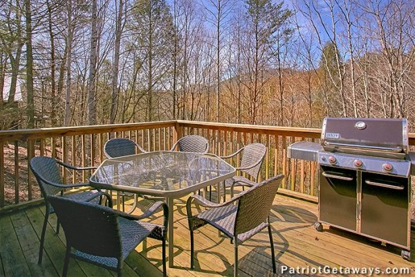 Grill and table on a deck at Stags Leap, a 2 bedroom cabin rental located in Pigeon Forge