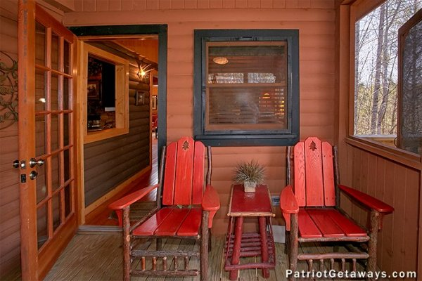 Red chairs on a covered porch at Stags Leap, a 2 bedroom cabin rental located in Pigeon Forge