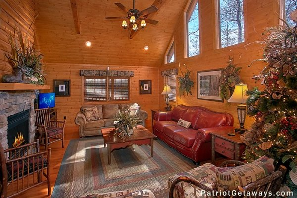 Living room with see-through fireplace and TV at Stags Leap, a 2 bedroom cabin rental located in Pigeon Forge