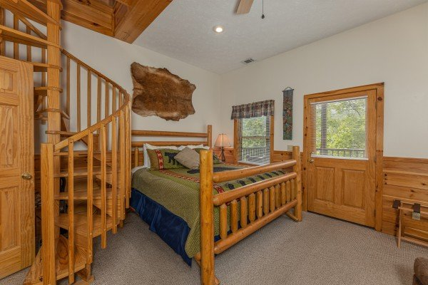 Bedroom with a spiral staircase and deck access at Honeysuckle Hideaway, a 1 bedroom cabin rental located in Pigeon Forge