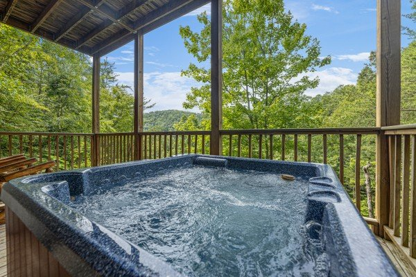 Hot tub on a covered deck at Honeysuckle Hideaway, a 1 bedroom cabin rental located in Pigeon Forge