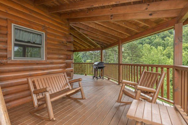 Rocking chairs and rocking bench on a covered deck at Almost Bearadise, a 4 bedroom cabin rental located in Pigeon Forge