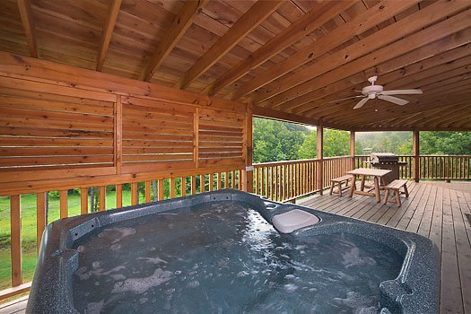 Hot tub sits under a covered deck with ceiling fans at Almost Bearadise, a 4 bedroom cabin rental located in Pigeon Forge