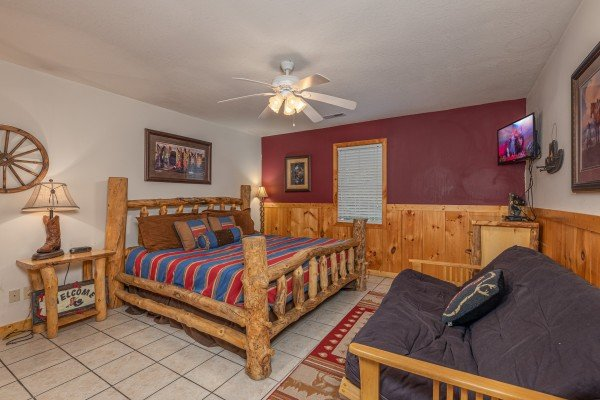 King log bed and a futon on the first floor at Almost Bearadise, a 4 bedroom cabin rental located in Pigeon Forge