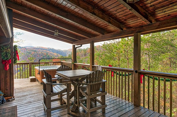 Covered deck with dining table for four at R & R Hideaway, a 1 bedroom cabin rental located in Pigeon Forge