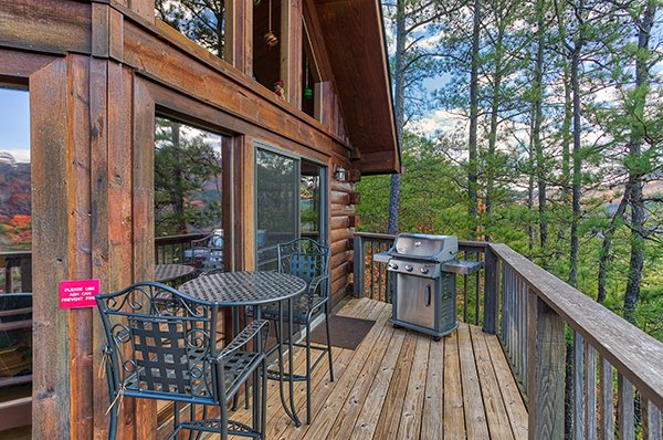 Bistro set for two and propane grill on a deck at R & R Hideaway, a 1 bedroom cabin rental located in Pigeon Forge