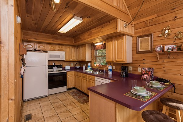 Kitchen with white appliances and counter seating for two at R & R Hideaway, a 1 bedroom cabin rental located in Pigeon Forge