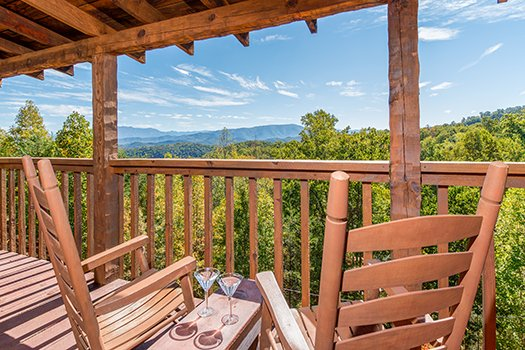 two rocking chairs with drinks on the table overlooking mountains at a postcard view a 1 bedroom cabin rental located in pigeon forge