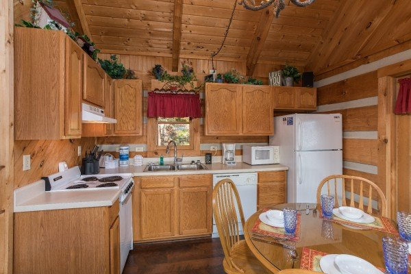 kitchen with white appliances and dining room table for four at a postcard view a 1 bedroom cabin rental located in pigeon forge