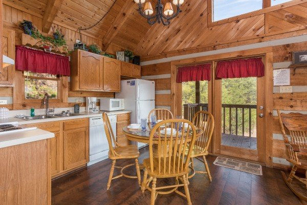 dining table with seating for four in the kitchen at a postcard view a 1 bedroom cabin rental located in pigeon forge