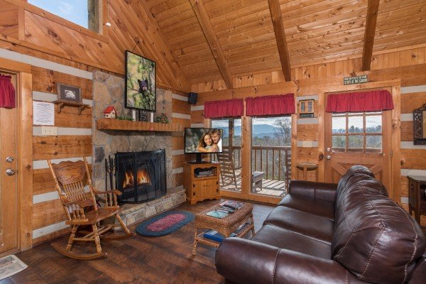 living room with fireplace and television a postcard view a 1 bedroom cabin rental located in pigeon forge
