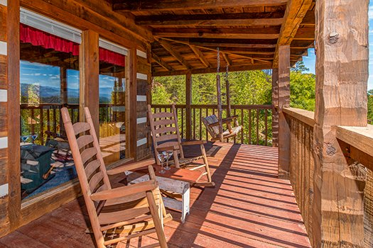 rocking chairs and a porch swing on a covered deck at a postcard view a 1 bedroom cabin rental located in pigeon forge