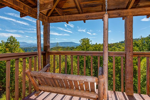 porch swing on a covered porch at a postcard view a 1 bedroom cabin rental located in pigeon forge