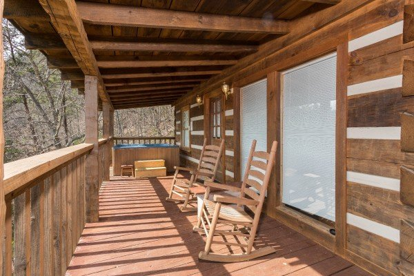 rocking chairs on a covered deck at a postcard view a 1 bedroom cabin rental located in pigeon forge