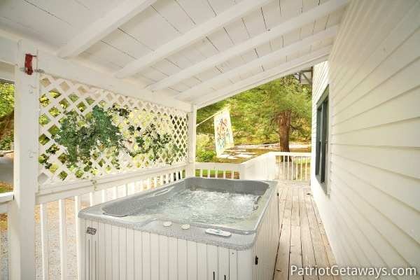 Hot tub on the covered deck at Dolly's Adorable River Cottage, a 3-bedroom cabin rental located in Pigeon Forge