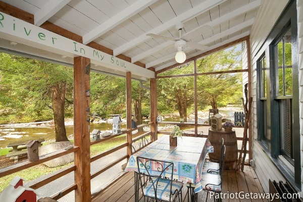 Patio dining on screened deck at Dolly's Adorable River Cottage, a 3-bedroom cabin rental located in Pigeon Forge