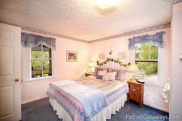 bedroom with queen sized bed at dolly's adorable river cottage a 3 bedroom cabin rental located in pigeon forge