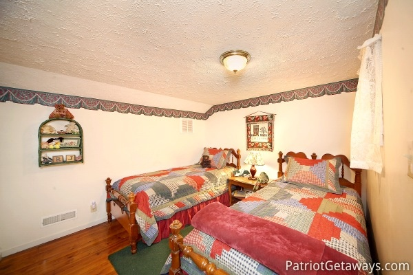 Two twin beds in bedroom at Dolly's Adorable River Cottage, a 3-bedroom cabin rental located in Pigeon Forge