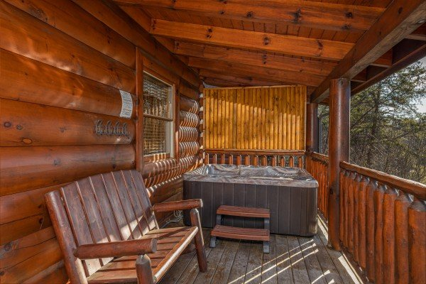Bench and hot tub on the covered deck at Southern Comfort Memories, a 2 bedroom cabin rental located in Pigeon Forge