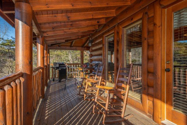Rocking chairs on a covered deck at Southern Comfort Memories, a 2 bedroom cabin rental located in Pigeon Forge