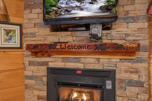 Welcome sign over the fireplace and under the TV at Southern Comfort Memories, a 2 bedroom cabin rental located in Pigeon Forge