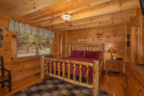 Bedroom with a log bed, night stand, and lamp at Southern Comfort Memories, a 2 bedroom cabin rental located in Pigeon Forge