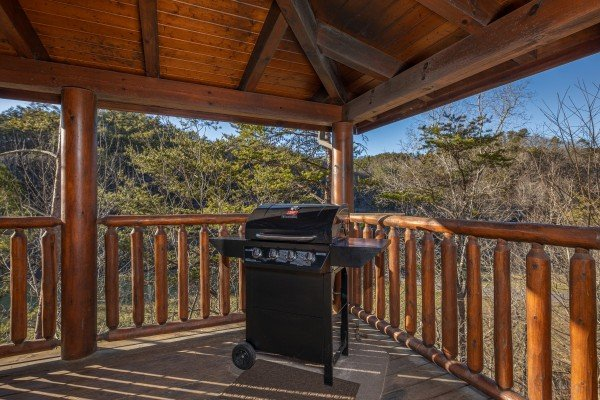 Gas grill on a covered deck at Southern Comfort Memories, a 2 bedroom cabin rental located in Pigeon Forge